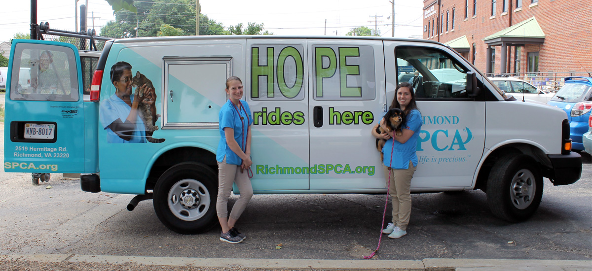"Admissions counselors standing in front of transfer van. Side of van says ""Hope rides here."""