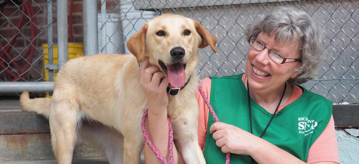 volunteer Sheila Weisensale with Daphne, a yellow Labrador retriever mix