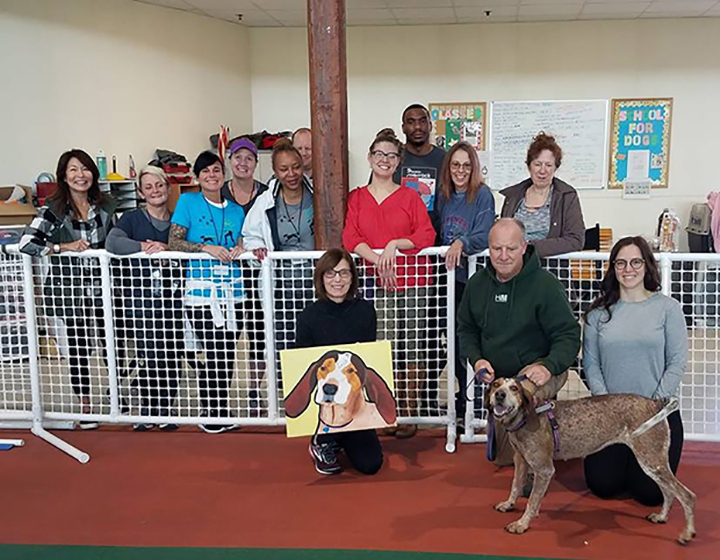 Hannah's adopters kneel with her in the Track and Training Center with staff and volunteers standing behind them