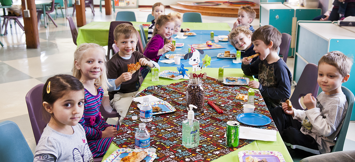 Nine Children Seated At A Long Table Eating Pizza During Birthday Party