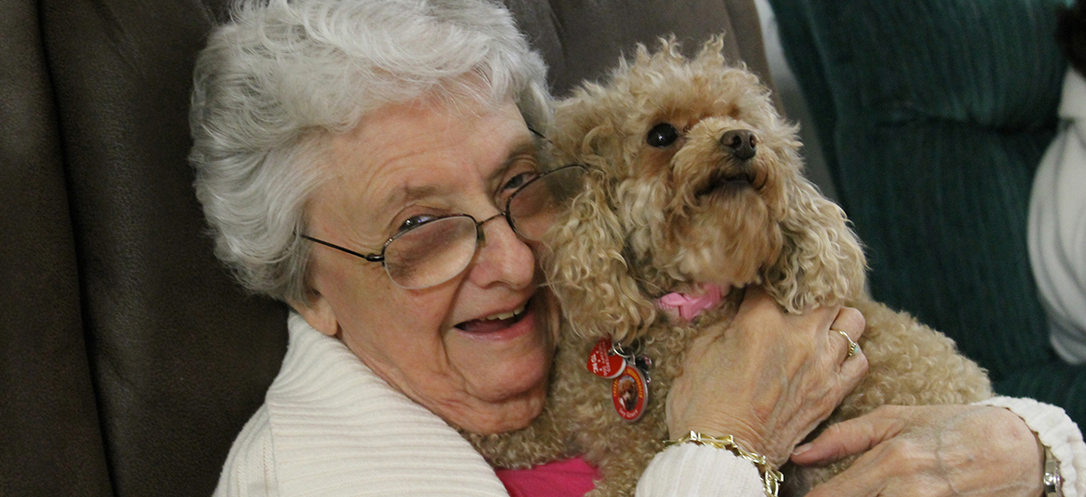 elderly woman smiles while embracing miniature poodle