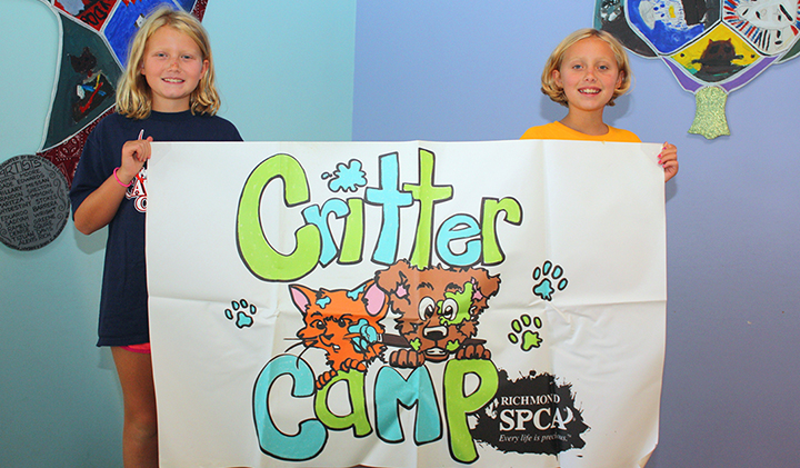 """Two girls hold up a banner that says """"Critter Camp"""" with illustrations of a cat and dog and the Richmond SPCA logo"""