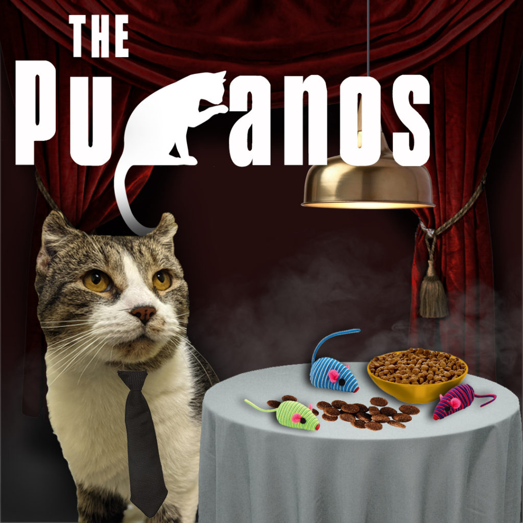 """Cat with white and tabby markings, wearing a neck tie, sits next to a table draped with a white table cloth. On the table are several toy mice and a bowl of cat food. Behind this scene are red curtains pulled back with gold tassels. White text overlay """"The Puranos"""" is styled like """"The Sopranos."""""""